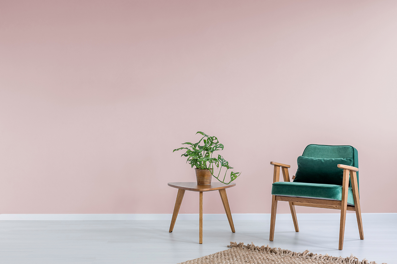 pink room with green arm chair and coffee table with a plant
