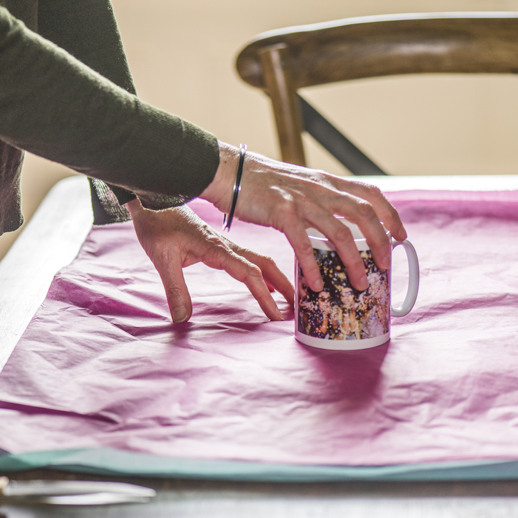 hands placing a mug on tissue paper ready for wrapping