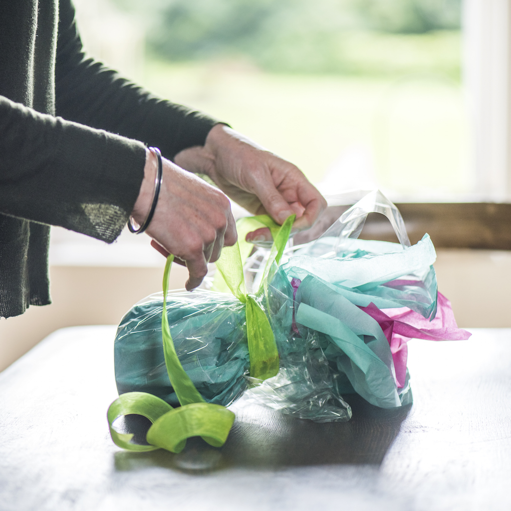 hands wrapping a present using tissue paper, cellophane and ribbon