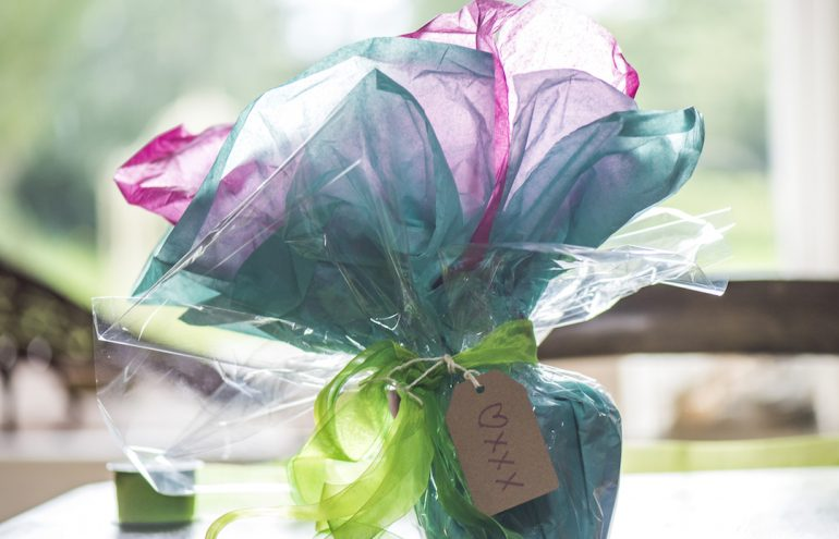 a gift wrapped with blue and pink tissue paper and cellophane with a label