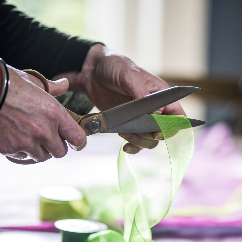 hands using a pair of large scissors cutting green ribbon wrapping a gift