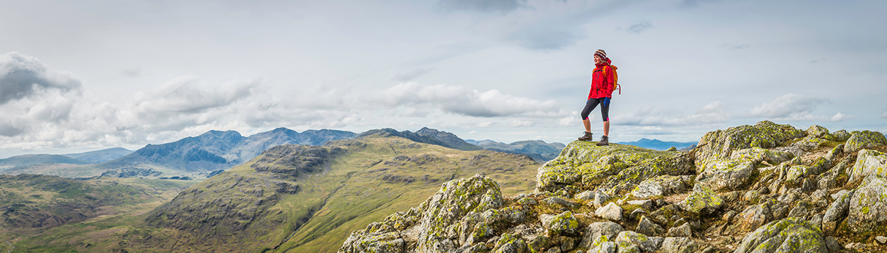 Teenage girl hiker standing on a mountain summit overlooking a panoramic vista of green valleys and rocky peaks high in the picturesque natural landscape of the Lake District National Park, Cumbria, UK. ProPhoto RGB profile for maximum color fidelity and gamut.