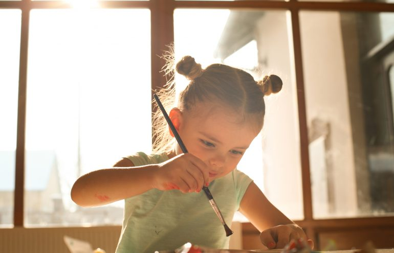 Little girl painting with paint brush at home.