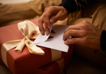 A man's hands closing an envelope next to a wrapped christmas present