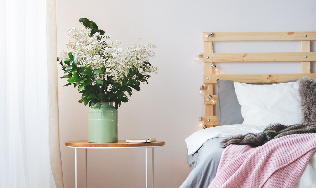Modern bed and small nightstand with bunch of flowers in cozy bedroom
