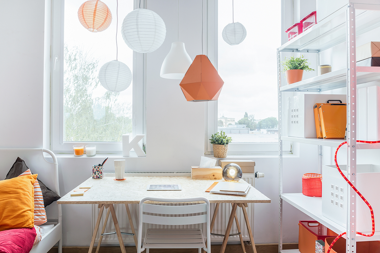 Space for learning in modern teenager's room with paper lanterns hanging from ceiling