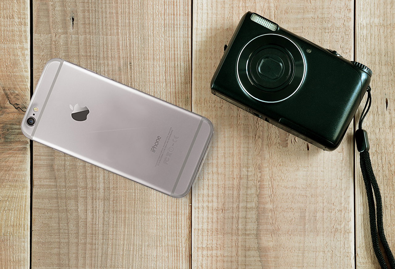 Black compact digital camera and iphone 6 on wooden background.