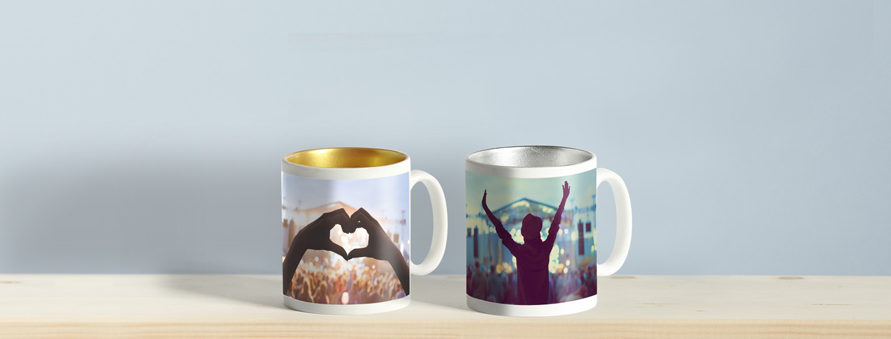 one silver mug, one gold mug with concert photos