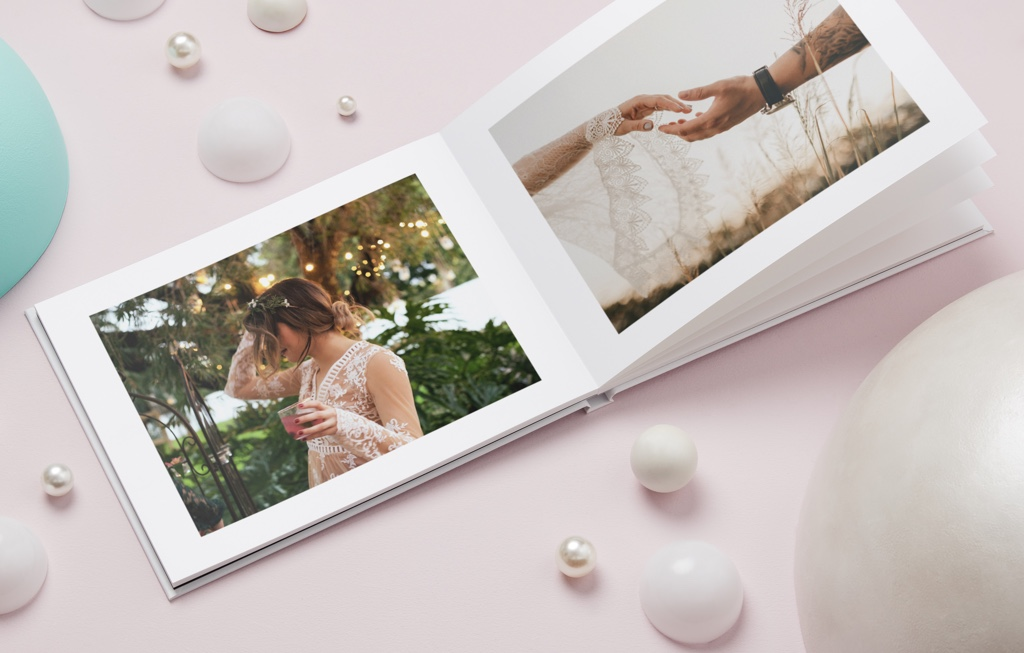 A3 Layflat Photo book laying open showing a bride holding a drink on one page and a couples hands on the other page